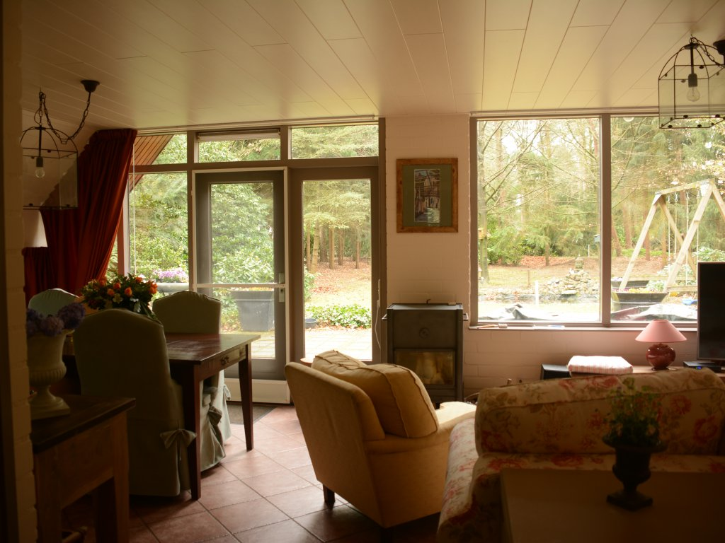 Huiskamer met links grote eettafel en houtkachel